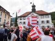 Mit einer Acht-mal-Acht-Meter grossen Fahne am Rathaus in Moutier wollen die Teilnehmer einer Veranstaltung die Zugehörigkeit zum Kanton Jura untermauern. (Bild: KEYSTONE/JEAN-CHRISTOPHE BOTT)