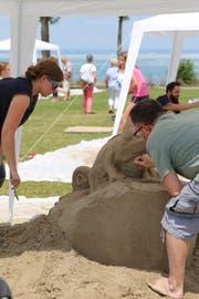 Der 1. Familien-Sandskulpturen-Wettbewerb hat nebst den Teilnehmenden auch viele Zuschauer zum Horner Festplatz gelockt. Im Bild die Arbeiten an der Chamäleon-Skulptur, die später siegte. (Bild: Martin Rechsteiner)