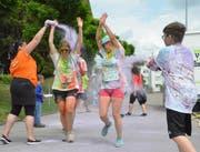 Helfer färben vorbeirennende Teilnehmerinnen.
