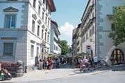 Blick in die St.-Oswalds-Gasse (grosses Bild), musikalische Unterhaltung (rechts oben) und ein gefragter Büchermarkt (rechts unten). (Bild: Bilder: Maria Schmid (Zug,16. Juni 2018))
