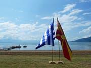 Die Flaggen Griechenlands und der Republik Nord-Mazedonien am Ufer des Prespasees, wo die Unterzeichnung einer Vereinbarung zum Namensstreit stattfand. (Bild: KEYSTONE/EPA/NAKE BATEV)