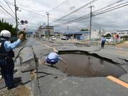 Arbeiter checken die Schäden durch ein Erdbeben an einer Strasse. (Bild: KEYSTONE/EPA-EFE/JIJI PRESS)