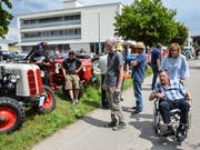 Heimbewohner und auswärtige Besucher begutachten die aufgereihten alten Traktoren. (Bild: Christoph Heer)
