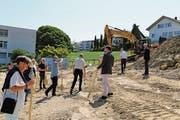 Der Bagger steht bereit für den Beginn der Bauarbeiten. Hans Bereuter (Mitte) macht mit dem Spaten den Anfang. (Bild: Rebecca Frei)