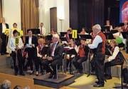Dirigent Guido Weber (Mitte) erhielt am Konzert ein Geschenk für sein Jubiläum. (Bild: Flavia Niederberger; Engelberg, 16. Juni 2018)