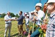 Der Roggwiler Gemeindepräsident Gallus Hasler übergibt die Baubewilligung an Projektplaner Sandro Nater. (Bild: Donato Caspari)