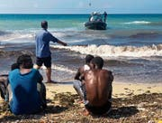 Afrikanische Migranten warten auf ein Rettungsboot an der libyschen Küste. Bild: AP (Tripoli, 20. Juni 2018)