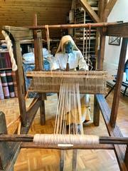 Eine Weberin am Webstuhl, eingekleidet nach dem Vorbild der damaligen Zeit.