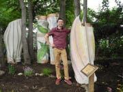 Vom Kunstwerk zum Pizzabelag: Der New Yorker Künstler Brian Soliwoda mit seinen Holzskulpturen, aus denen in den kommenden Monaten essbare Pilze wachsen sollen. (Bild: Keystone/dpa/Johannes Schmitt-Tegge)