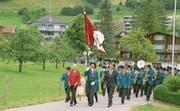 Die neue Fahne wird präsentiert. Fahnengotte Heidi Abächerli (rotes Oberteil) und –Götti Peter Wälti (im dunklen Anzug) marschieren neben Fähnrich Hans Achermann. (Bild: Primus Camenzind (Giswil, 24. Juni 2018))