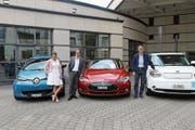 Regula Hürlimann, Georges Helfenstein und Peter Hausherr posieren mit den Elektroautos. (Bild: Gemeinde Cham (25. Juni 2018))
