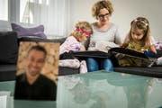 Martina zeigt ihren Mädchen im Fotoalbum Bilder ihres Papas. (Bild: Reto Martin)