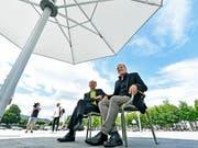 Endlich: Die Zürcher Stadträte Richard Wolff (links) und Filippo Leutenegger (rechts) können auf dem Sechseläutenplatz unter einem robusten Sonnenschirm den Schatten geniessen. Das Vorgängermodell war vom Winde verweht und zerzaust worden. (Bild: KEYSTONE/WALTER BIERI)