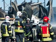 Feuerwehrleute überwachen am Donnerstag die Brandstätte auf dem Gelände der Sägerei Despond, die dem Freiburger SVP-Nationalrat Jean-François Rime gehört. (Bild: KEYSTONE/THOMAS DELLEY)