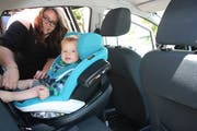 Autositz-Verkäuferin Jessica Lombardi mit ihrem Sohn, der die Reisen jeweils rückwärts fahrend mitmacht (Bild: Simon Dudle)