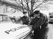 Polizisten besprechen sich zur Suche nach der verschwundenen Edith Trittenbass vor deren Schulhaus in Wolfikon. (Bild: KEYSTONE/STR)