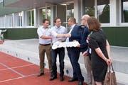 Adrian Nussbaumer von der Nussbaumer Holz AG überreicht der Vertretung von Gemeinde und Schule in einem symbolischen Akt den Schlüssel für den neuen Pavillon.(Bild: Maria Schmid ( Cham, 29. Juni 2018 ))