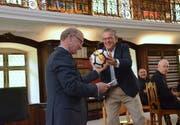 Eines der Geschenke, welche Klosterdirektor Werner Ibig (links) dem abtretenden Präsidenten des Vereins Kloster Fischingen, Roman Müggler, überreichte. (Bild: Christoph Heer)