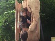 Der Performance-Künstler Abraham Poincheval winkt ein letztes Mal aus der Holzstatue heraus, bevor der Deckel für eine Woche zugeht. Zum Essen hat er Nüsse und Trockenfrüchte dabei. (Screenshot YouTube) (Bild: Screenshot YouTube)
