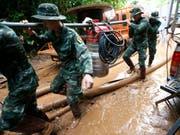 Suchmannschaften pumpen mit schweren Geräten Wasser aus der Höhle ab. (Bild: KEYSTONE/AP/SAKCHAI LALIT)