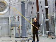 Unter der Regenanlage im Hochspannungslabor der ETH Zürich können die Forschenden das Verhalten von hybriden Stromleitungen genau untersuchen. (Bild: ETH High Voltage Lab/Jurij Pachin)