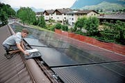 Andreas Rohrer von der Firma Odermatt + Sicher AG montiert die Solar-Panels auf dem Dach des Pfadiheims. (Bild: Corinne Glanzmann (Stans, 29. Mai 2018))