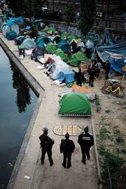 Polizisten beobachten die Räumung eines Flüchtlings-Zeltlagers in Paris. (Bild: François Mori/AP (4. Juni 2018)
