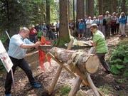 Symbolische Eröffnung des Naturpfads der Sinne: Stiftungsratsmitglied Regina Dörig und Regierungsrat Alfred Stricker zersägen einen Baumstamm. (Bild: Matin Hüsler)