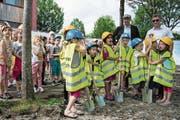 Die Kinder und damit die künftigen Nutzer der Neubauten standen am gestrigen Baustart im Fokus. Im Hintergrund sind Architekt Peter Moor (links) und Gemeinderat Markus Scheidegger zu sehen. (Bild: PD/Hans Galliker)