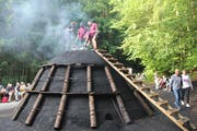 Mitarbeiter der Kartause bringen der Köhlerin Doris Wicki glühende Kohle zum Anfachen des Meilers. (Bild: Christine Luley)
