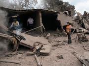 Feuerwehrleute suchen in mit Asche zugedeckten Trümmern nach Opfern des Vulkanausbruchs in der guatemaltekischen Ortschaft Escuintla. (Bild: KEYSTONE/AP/RODRIGO ABD)