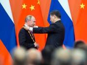 Chinas Präsident Xi Jinping ehrt seinen Gast aus Russland, Wladimir Putin, mit der erstmals verliehenen goldenen Ehrenmedaille. (Bild: KEYSTONE/AP POOL/ALEXANDER ZEMLIANICHENKO)