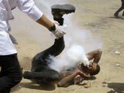 Anhaltende Gewalt in Nahost: Ein verletzter Palästinenser nach dem Beschuss durch einen Tränengas-Behälter durch die israelische Armee im Gazastreifen am Freitag. (Bild: KEYSTONE/AP/ADEL HANA)