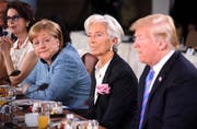 Kanzlerin Angela Merkel und IWF-Direktorin Christine Lagarde können ihren Missmut über Trumps verspätetes Erscheinen nicht verbergen. (Bild: Leon Neal/Getty Images)