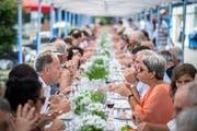 """Die Gäste beim Essen am """"langen Tisch"""". (Bild: Reto Martin)"""
