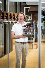 Unternehmer Dario My steht im Raum, wo die Kuckucksuhren zwei bis drei Wochen lang Probe laufen, ehe sie versendet werden. Er präsentiert ein noch grösseres Modell. (Bild: Reto Martin)