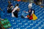 Japanische Fans räumen im Stadion auf. (Bild: AP Photo/Pavel Golovkin)