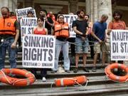In Italien haben sich Demonstranten am Verkehrsministerium festgekettet. Sie protestieren damit gegen das Hafenverbot für Rettungsschiffe. (Bild: KEYSTONE/AP/ALESSANDRA TARANTINO)