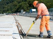 Schluss mit langen Hosen bei grösster Hitze im Strassenbau: Ab sofort dürfen Bauarbeiter kurze Hosen tragen. (Bild: KEYSTONE/ANTHONY ANEX)