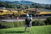 Bauen vor Publikum: Arbeiter heben die Gleise der Bahnstrecke in Winkeln mit einem grossen Bauzug an. (Bild: Benjamin Manser)
