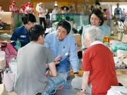 Japans Regierungschef Shinzo Abe (Mitte) spricht den Betroffenen der Unwetterkatastrophe Mut zu. (Bild: KEYSTONE/AP Kyodo News/SHOHEI MIYANO)