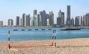 Ein Tor im Wüstensand vor der Skyline von Doha, der Hauptstadt des Emirats Qatar. (Bild: Keystone)