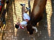 Einer der gehetzten Bullen bei der Stierhatz im spanischen Pamplona schleift einen Läufer an dessen Halstuch mit sich. (Bild: KEYSTONE/EPA/RODRIGO JIMENEZ)