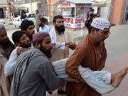 Helfer bringen ein verletztes Opfer des Anschlages in Pakistan in Sicherheit. (Bild: KEYSTONE/EPA/JAMAL TARAQAI)