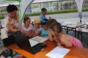Daniela Gröbli, Autorin des Goldi Büchleins, schart zahlreiche Kinder um sich, die ihr beim Erzählen aufmerksam zuhören. (Bild: Rosmarie Berlinger, Buochs, 14. Juli 2018)