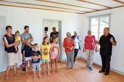 Kirchenpräsident Martin Dönni (rechts) zeigt einer Besuchergruppe das frisch renovierte Pfarrhaus. (Bild: Christoph Heer)