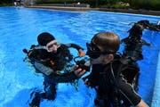 Tauchen im Amriswiler Schwimmbad: Kursleiter Ahmed Oswald instruiert Teilnehmer Noe (11) beim Einsetzen des Mundstücks. (Bild: Manuel Nagel)