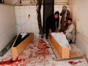 Verwandte betten ein Opfer eines Selbstmordanschlags in Kabul in einen Sarg - Noch nie wurden in Afghanistan so viele Zivilisten bei Gefechten oder Anschlägen getötet wie im ersten Halbjahr 2018. (Bild: KEYSTONE/EPA/HEDAYATULLAH AMID)