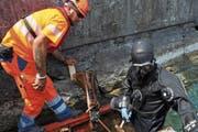 Baustellenchef Marcel Schmidiger und Taucher Reto Rohrer von der Kibag Bauleistungen AG setzen Schalelemente für Unterwasser-Betonarbeiten an der seitlichen Ufermauer. (Bild: Matthias Piazza (Buochs, 12. Juli 2018))