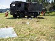 Polizisten untersuchen das in Linden BE verunfallte Transportfahrzeug der Armee, nachdem dieses wieder aufgerichtet worden ist. (Bild: Keystone/Peter Schneider)